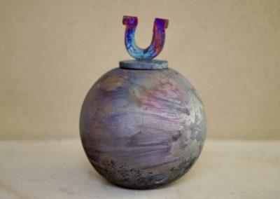 1502-Urn met hoefijzer middel. €115,-